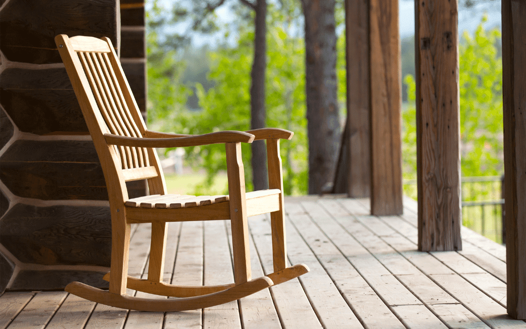 Wooden rocking chair empty on a verandah bordering the woods